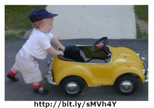 The child is applying an unbalanced force to the car resulting in moving the car.